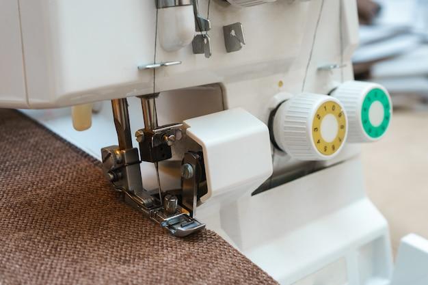 Matériel professionnel. pied de pression de machine à coudre surjeteuse moderne utilisé avec un vêtement. gros plan photo.