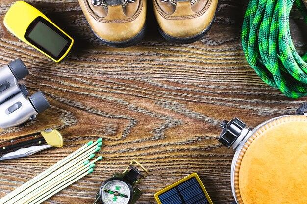 Matériel de randonnée avec bottes, boussole, jumelles, allumettes, sac de voyage sur woodentable. concept de mode de vie actif.