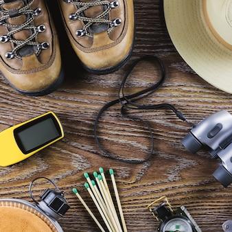 Matériel de randonnée ou de voyage avec bottes, boussole, jumelles, allumettes sur fond de bois. concept de mode de vie actif
