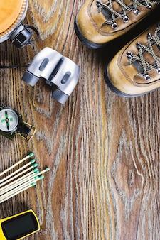 Matériel de randonnée ou de voyage avec bottes, boussole, jumelles, allumettes sur fond de bois. concept de mode de vie actif.