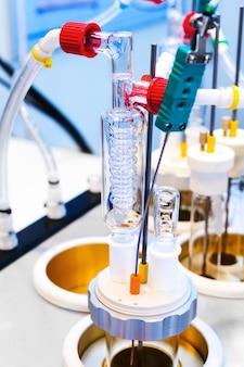 Matériel de recherche en laboratoire. fragment avec capteurs et réfrigérateur à spirale en verre. distillateur chimique en verre.