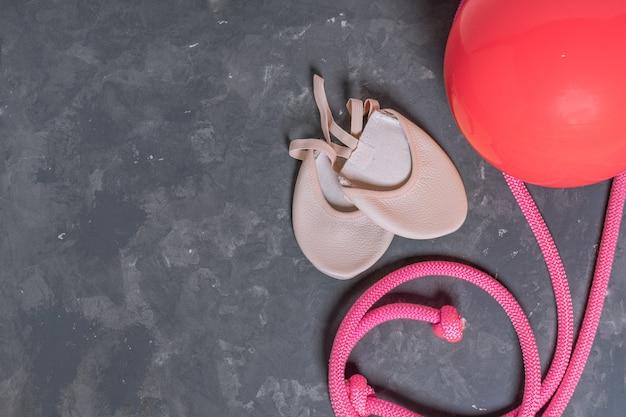 Matériel rythmique qymnastique. corde à sauter rose, ballon et chaussures de gymnastique vue de dessus sur fond gris