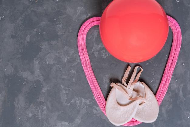 Matériel rythmique qymnastique. corde à sauter rose, ballon et chaussures de gymnastique vue de dessus sur gris