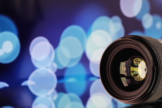 Matériel vidéaste et photographe. lentilles sur la table sur fond de lampes lumineuses. éblouissement et bokeh dans le reflet de la vitre de l'appareil photo.