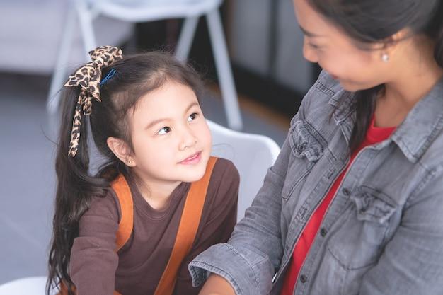 Maternelle parle en souriant à une enseignante