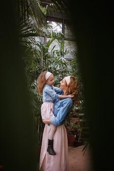 Maternité et émotions de bonheur et joie de la mère et de la fille. une jeune mère tient sa petite fille heureuse dans ses bras, la soulevant et la regarde dans le contexte de la verdure
