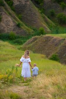 Maternité. mère et bébé ensemble main dans la main. maman et son fils marchent par la main sur le terrain. fête des mères. belle nature avec des gens. marcher ensemble par la main