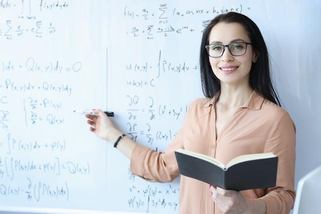 Mathématicien de femme avec des lunettes debout au tableau noir avec des formules et tenant un livre ouvert