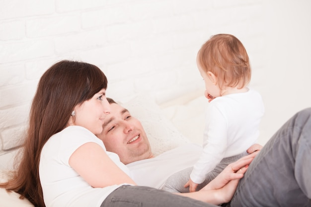 Matin au lit, jeune famille avec bébé bébé dans la chambre