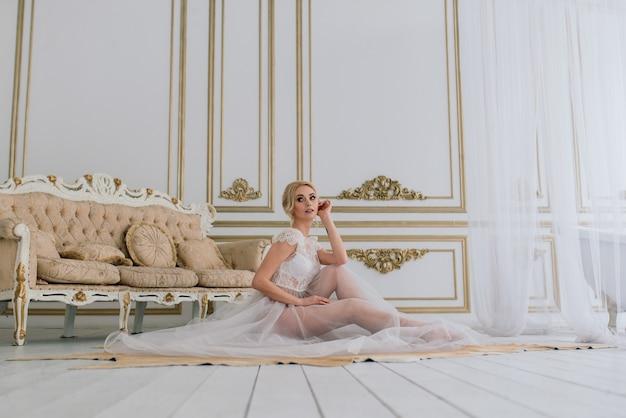 Matin d'une belle jeune mariée dans une robe boudoir
