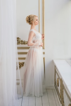 Matin d'une belle jeune mariée en robe boudoir. studio, intérieur.