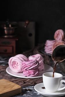 Matin avec café et zéphyrs sur une assiette. dessert aux fruits sur une vieille table en bois. guimauves aux pommes avec purée de baies et expresso.