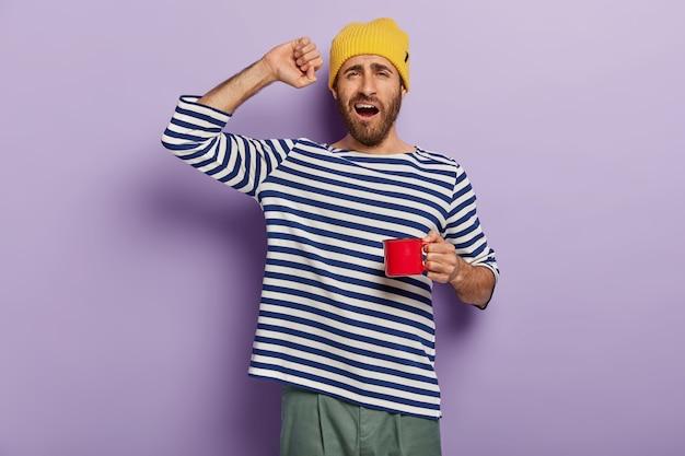 Le matin commence par le café. un homme endormi s'étire après son réveil, boit une boisson chaude pour se sentir rafraîchi, tient une tasse rouge, dit bonjour