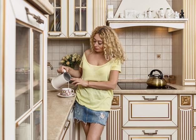 Matin dans la cuisine. la femme verse le lait dans la tasse.