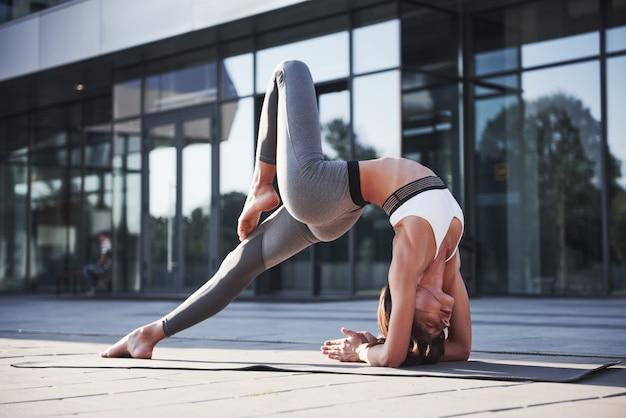 Matin d'été ensoleillé. jeune femme athlétique faisant le poirier sur la rue du parc de la ville parmi les bâtiments urbains modernes. faites de l'exercice en plein air mode de vie sain