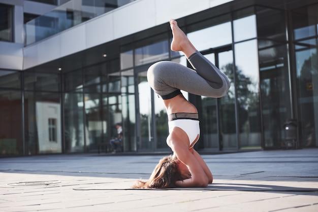 Matin d'été ensoleillé. jeune femme athlétique faisant le poirier sur la rue du parc de la ville parmi les bâtiments urbains modernes. faites de l'exercice en plein air avec un mode de vie sain.