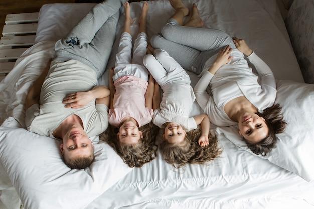 Matin famille : les enfants avec les parents jouant au lit. se réveiller d'un rêve. je viens de me réveiller. amour