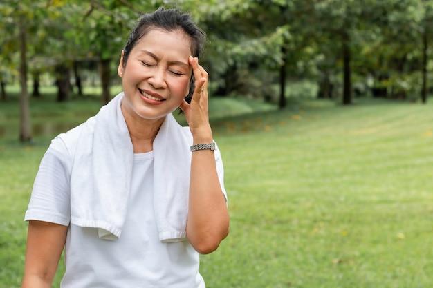 Le matin. femme âgée maux de tête asiatique pendant l'exercice au parc.