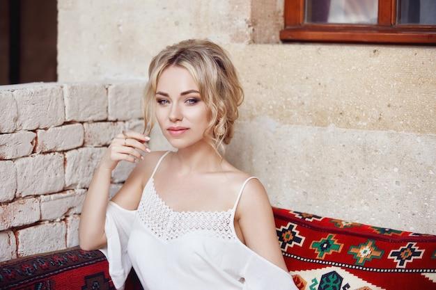 Matin girl reposant assis sur un canapé turc. une femme en vêtements légers se prépare à l'arrivée de son homme bien-aimé.