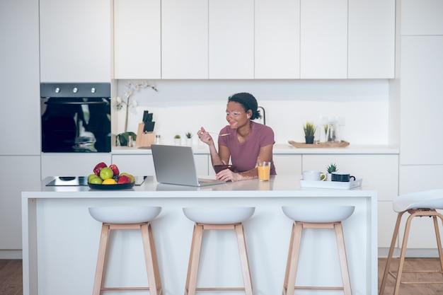 Matin à la maison. jeune femme à la peau foncée prenant son petit déjeuner à la maison et regardant quelque chose sur un ordinateur portable
