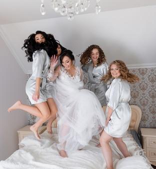 Matin de mariage, mariée avec demoiselles d'honneur saute joyeusement sur le lit et sourit