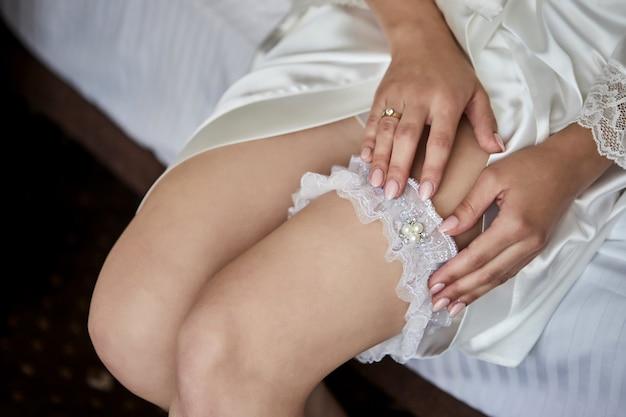 Matin de la mariée quand elle porte une jarretière de mariage sur la jambe, la femme se prépare avant la cérémonie