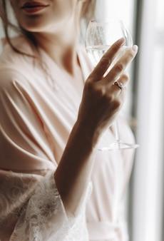Le matin de la mariée. séduisante mariée boit du vin blanc debout befo