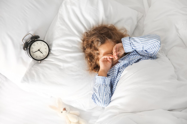 Matin de mignonne petite fille au lit