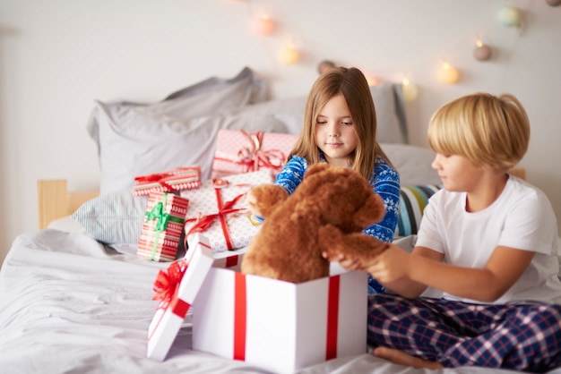 Matin ouvert des cadeaux de noël dans le lit