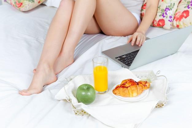Le matin et le petit déjeuner de la belle jeune fille au lit à la maison avec un ordinateur portable. gros plan des jambes de la fille