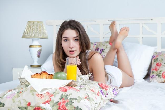 Le matin et le petit déjeuner de la belle jeune fille au lit à la maison