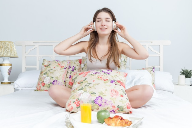 Matin et petit déjeuner de jeune belle fille au lit à la maison