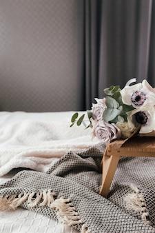 Matin romantique. table basse en bois avec des fleurs sur le lit avec couverture. roses lilas à l'eucalyptus et aux anémones. tons gris intérieurs.