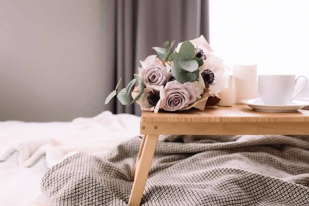 Matin romantique. table basse en bois avec des fleurs sur le lit avec plaid, tasse à café, fleurs et bougies. roses lilas à l'eucalyptus et aux anémones. tons gris intérieurs.