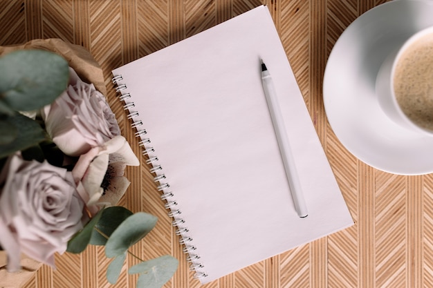 Matin romantique. table basse en bois avec des fleurs sur le lit à plat, tasse à café, fleurs, bloc-notes, stylo. roses lilas à l'eucalyptus et aux anémones.