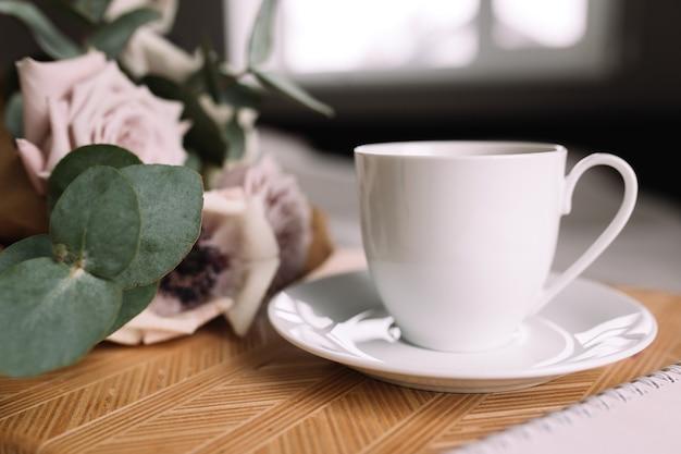 Matin romantique. table basse en bois avec fleurs sur lit, tasse à café, fleurs, bloc-notes, stylo. roses lilas à l'eucalyptus et aux anémones.