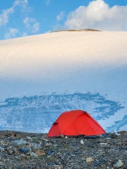 Matin, vue sur une tente renforcée orange sur fond de glacier sur un plateau de haute altitude. vue verticale.