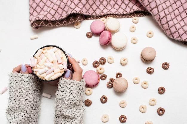 Matinée confortable avec latte et macarons. boisson chaude à la guimauve dans les mains de la femme, assortiment de bonbons colorés