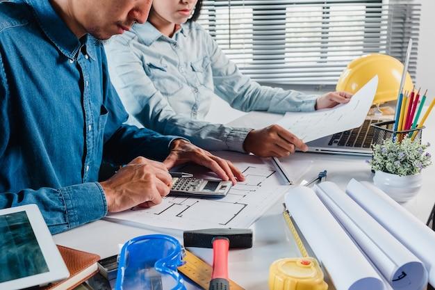 Mature architecte ingénieur homme à l'aide d'une calculatrice pour discuter de l'information avec un collègue plus jeune.