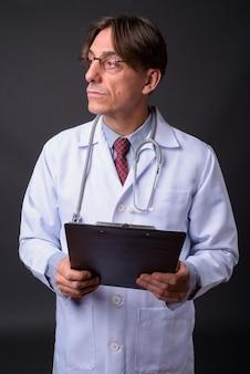 Mature bel homme italien médecin contre mur gris