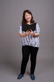 Mature, belle, asiatique, femme affaires, tenue, livre