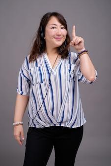 Mature belle femme d'affaires asiatique avec le doigt vers le haut