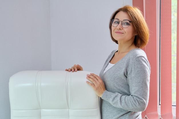 Mature belle femme d'affaires avec des lunettes, pull en cachemire près de fauteuil de bureau en cuir blanc
