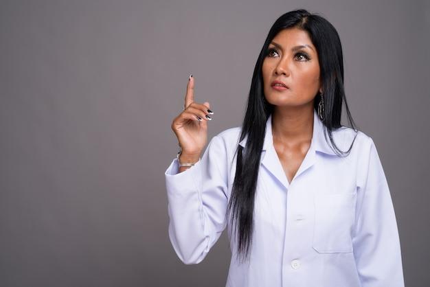 Mature belle femme asiatique médecin sur fond gris