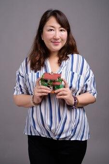 Mature belle femme asiatique tenant maison de jouet