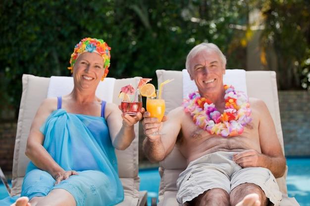 Mature couple buvant un cocktail au bord de la piscine