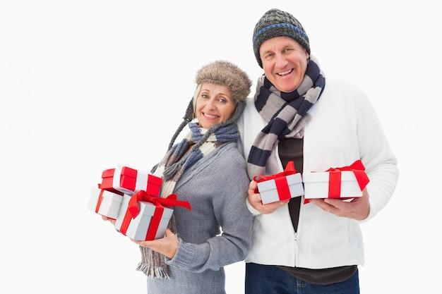 Mature couple en vêtements d'hiver tenant des cadeaux