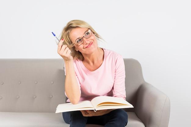 Mature femme assise sur un canapé tenant un stylo et un livre ouvert à la rêverie