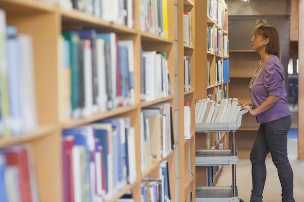 Mature femme bibliothécaire poussant un chariot dans la bibliothèque