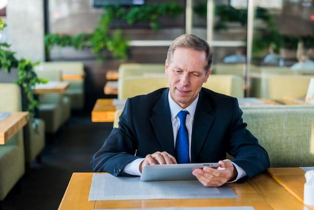 Mature homme d'affaires à l'aide de tablette numérique au restaurant